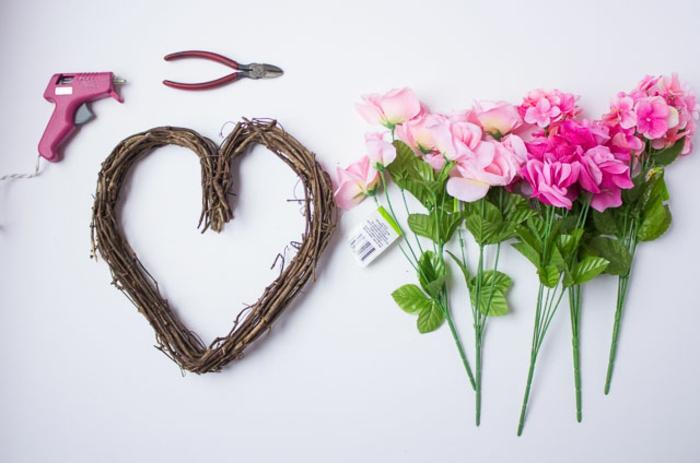 materiales necesarios para elaborar una encantadora guirnalda de flores en forma de corazon, forma de madera, pistola de pegamento, flores artificiales