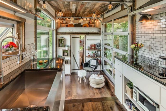 minicasas, planta única de una minicasa, cocina salón y dormitorio con cama lata, paredes con ladrillos y suelo de parquet