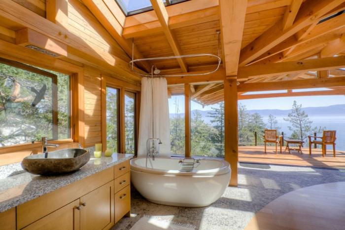 baño rústico con bañera oval moderna, lavabo típico para los baños rusticos, techo de madera y suelo de mármol
