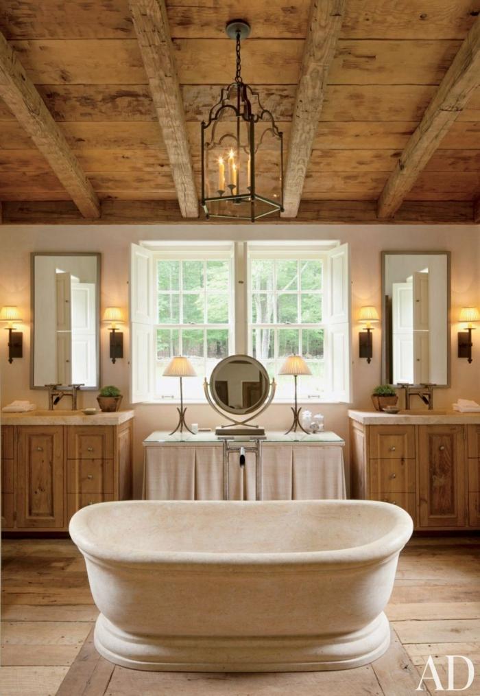 baños rusticos con aire cálido y acogedor, revestimiento de madera y bañera exenta, techo con vigas de madera y lámpara vintage