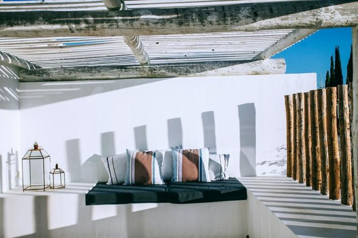 terraza atractiva en blanco con elementos de madera, cojines decorativas, techo de vigas de madera, sitio para relax