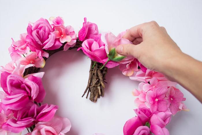 corona en forma de corazon decorada con rosas en color cyclamen y rosado artificiales, regalos para novios románticos y originales