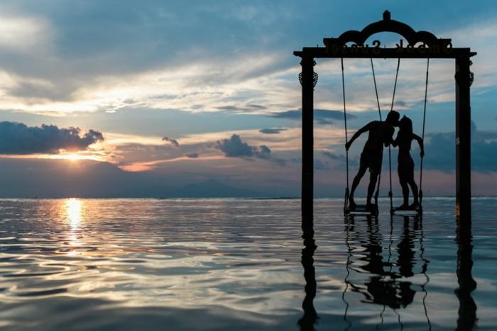 ideas de sorpresas divertidas para parejas para el dia de san valentín, columpios en el mar, pareja enamorada besándose