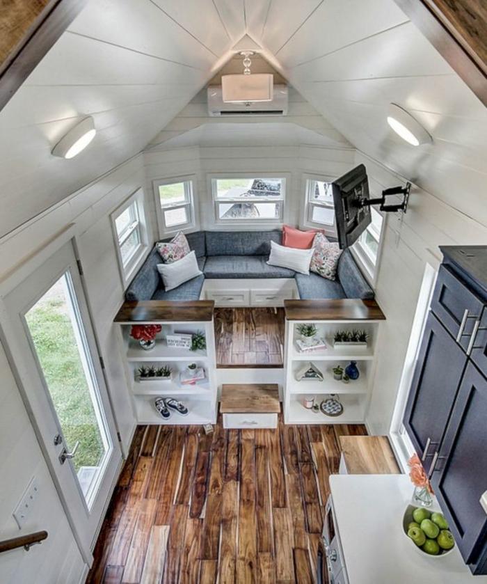 minicasas, vivienda funcional, dividida en dos habitaciones, salon acogedor con sofá en gris, estantería de madera y techo de madera