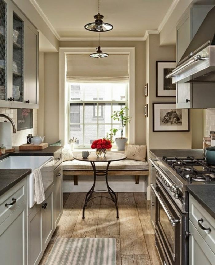 cortinas modernas, cocina larga y ancha decorada en beige, pequeña mesa oval de cristal, suelo de madera