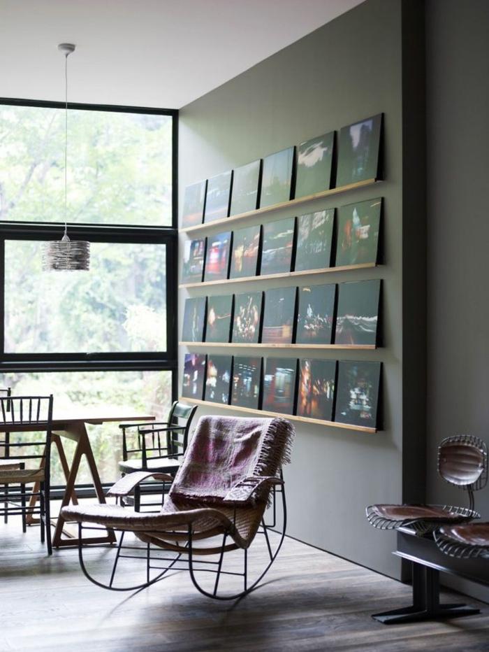 manualidades con fotos, precioso interior decorado en tonos oscuros, silla balancín original, pared en gris con fotografías nocturnas