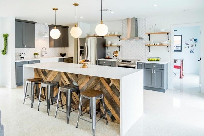 cocina en blanco con barra larga de madera pintada en blanca y muebles de cocina en gris, sillas metálicas y lámparas vintage