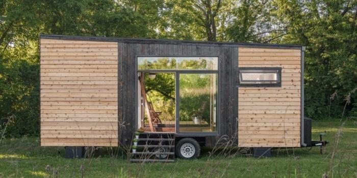 minicasas, ejemplo de una minicasa funcional y atractiva, vivienda en ruedas con revestimiento de madera colocada en el bosque