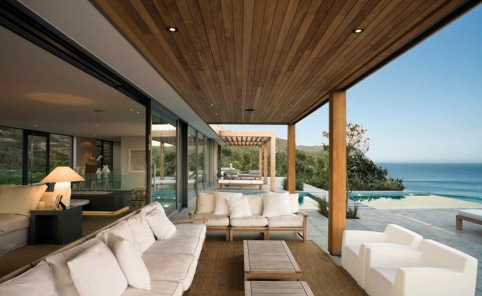muebles en blanco para terrazas modernas, terraza con vista, construcción de madera con lámparas empotradas, cojines decorativos en blanco