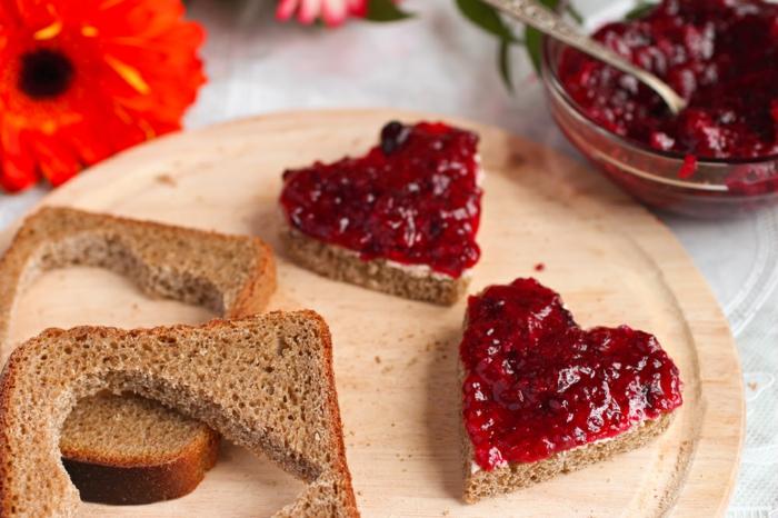tostadas cortadas en forma de corazón con mermelada roja y decoración de flores, propuesta para regalos originales para novios