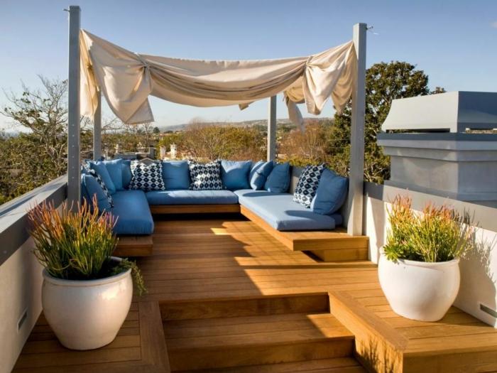 decoracion terrazas en tonos claros, muebles en azul celeste, cojines decorativos con motivos geométricos, grandes maceteros blancos con plantas verdes
