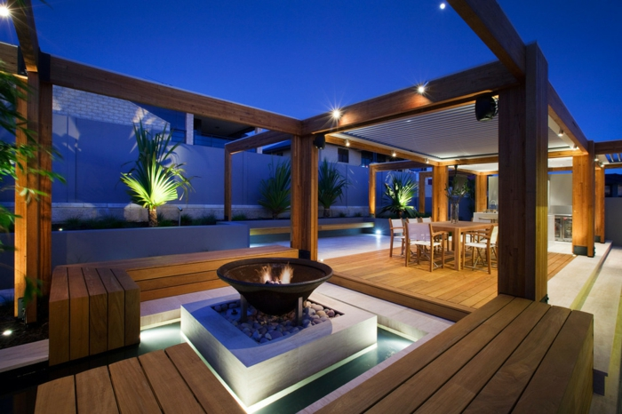 diseño innovador, grande terraza con elementos de madera, decoracion terrazas con lámparas empotradas, chimenea original, bancos de madera