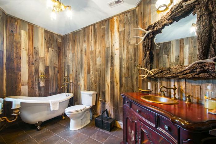 espacio decorado en estilo rústico, baños rusticos con paredes revestidas de madera y bañera vintage con patas garra, espejo original de madera