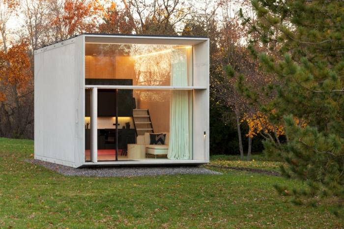 mini casas, ejemplo de casas prefabricadas de módulos de hormigón, forma cuadrada en color blanco, grandes ventanales que dividen ópticamente la casa