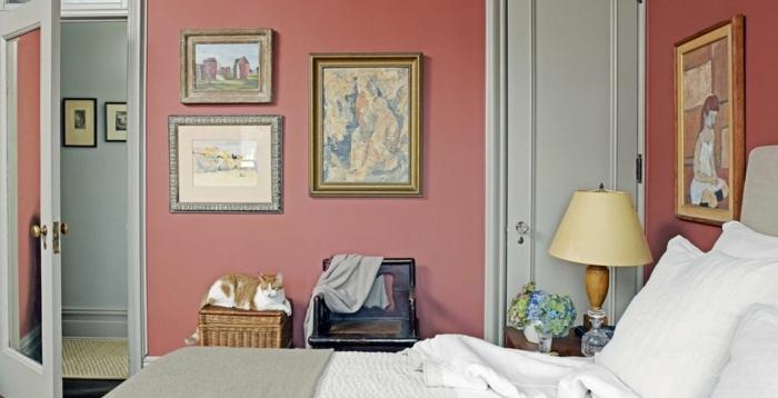 cuarto pequeño con cama doble, paredes pintadas en color salmón y preciosa decoración de cuadros clásicos