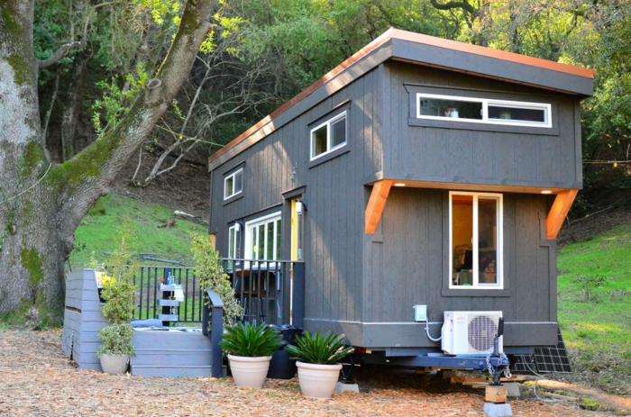 mini casas, casa de pequeño tamaño con cubierta de madera, grandes macetas con plantas, muchas ventanas pequeñas