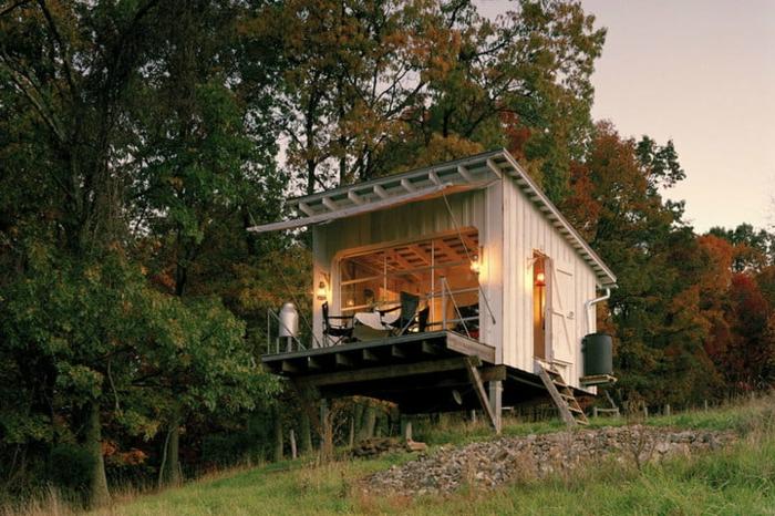 mini casas, bonita casa en blanco colocada en una plataforma de madera, paredes abatibles, casa prefabricada
