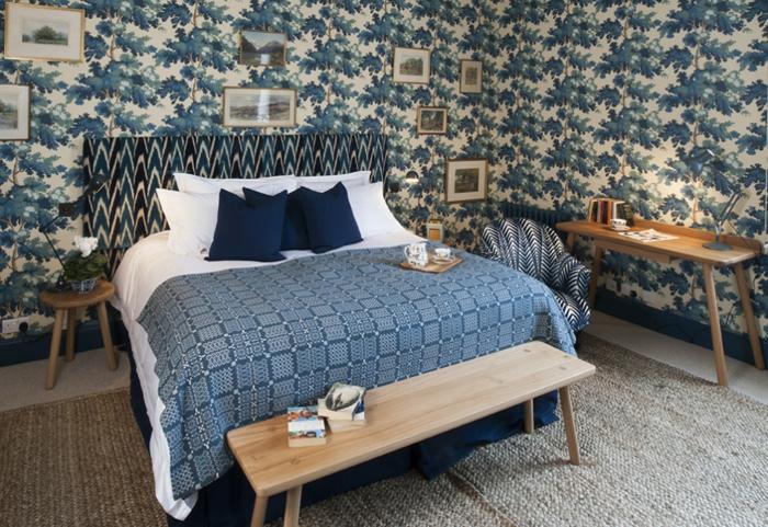 habitación en estilo vintage con muchos cuadros decorativos pequeños, cama con cabecero en estampado original
