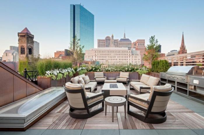 espaciosa terraza con muchos sillones, decoracion terrazas en beige, muchas plantas verdes y preciosa vista a la ciudad
