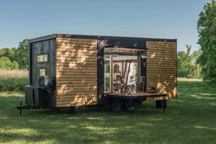mini casas, casa prefabricada de un diseño simple revestida de madera, terreno verde, pequeña plataforma de madera,