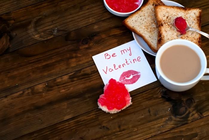 propuesta originales para regalos romanticos, desayuno con tostadas y café y hoja de papel con mensaje de amor