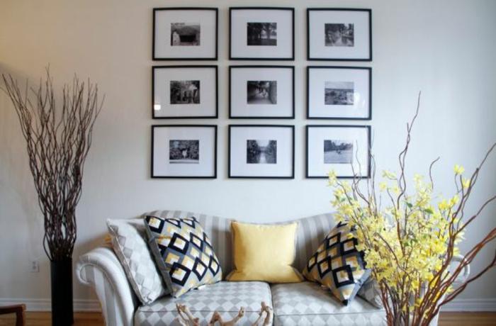 fotos originales, salón moderno con muebles tapizados con telas en motivos geométricos, pared en blanco decorada con cuadros en blanco y negro, plantas decorativas artificiales