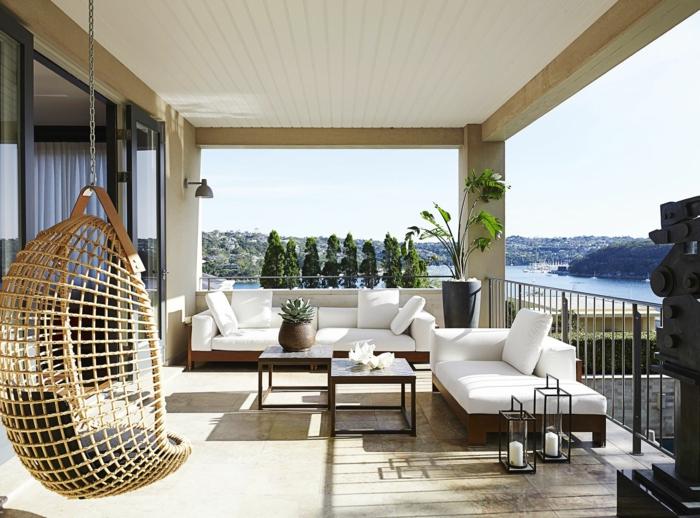 decorar terrazas con muebles modernos en blancos, silla de mimbre colgante, terrazas modernas con vistas