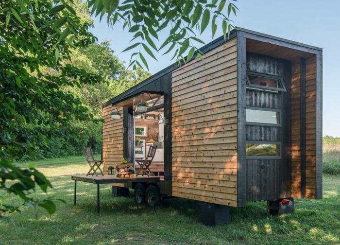 casas moviles, bonito ejemplo de casa prefabricada portatil colocada en un terreno verde, vivienda revestida de madera decorada de macetas colgantes