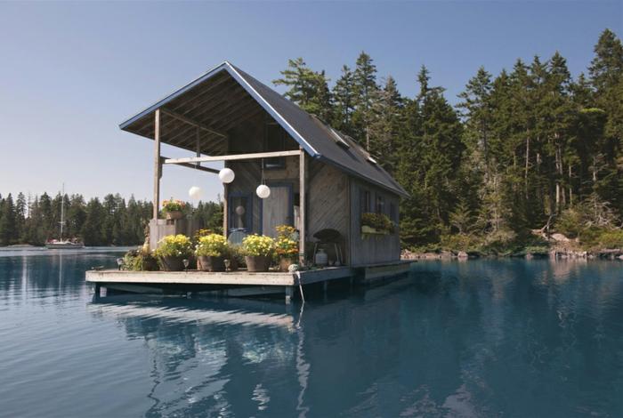 casas moviles, preciosa casa flotante de diseño asimétrico, vivienda colocada en una plataforma de madera, decoración de grandes macetas con flores