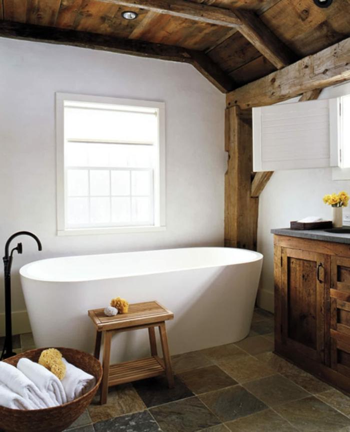 elementos típicos para un baño con decoracion rustica, bañera moderna exenta, paredes con vigas de madera y techo de madera con lámparas empotradas