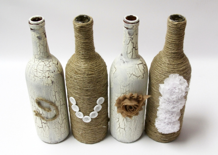 botellas de encanto decoradas con pintura y hilo cañamó, botellas en beige y blanco con flores deocrativos