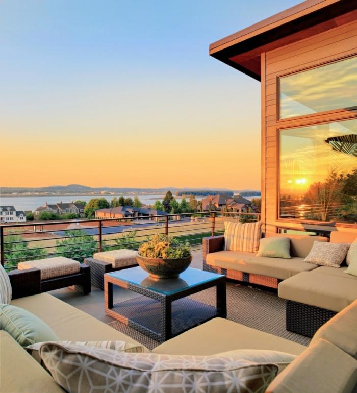 fabulosas ideas para decorar terrazas, muebles en beige, mesa de diseño moderno en negro decorada con un macetero con plantas verdes