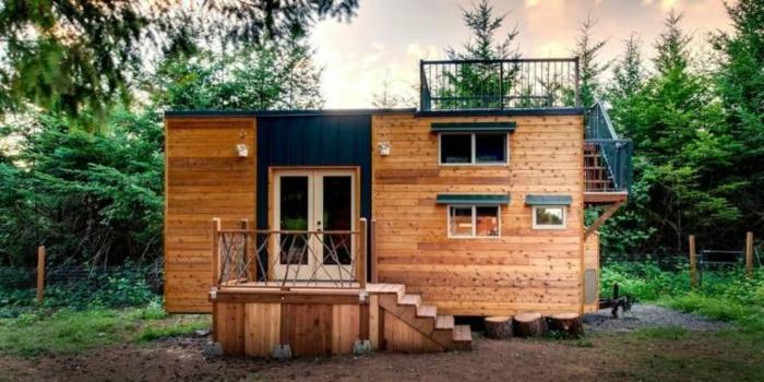 mini casas sobre ruedas, casa prefabricada de madera con terraza en el techo, muchas ventanas de diferente tamaño y construcción de madera con escaleras