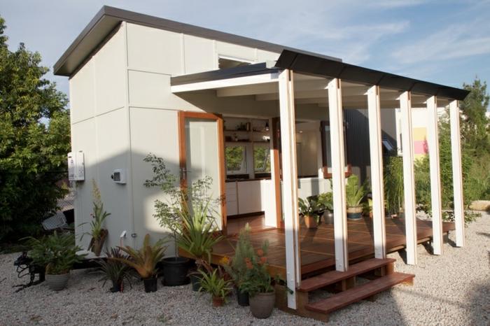 mini casas sobre ruedas, vivienda mínima con grande terraza, decoración de muchas macetas con plantas verdes, interior con cocina