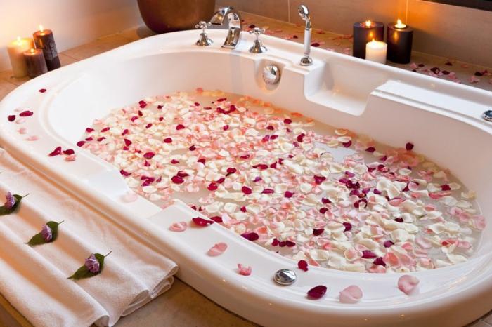propuestas sobre como sorprender a tu pareja para el dia de los enamorados, bañera llena de hojas de rosas en blanco, rosado y rojo