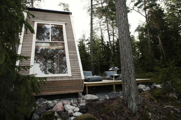 casas moviles, interesante idea de una cabaña en la montaña con grande ventanal y cubierta de madera, terreno con muchos árboles