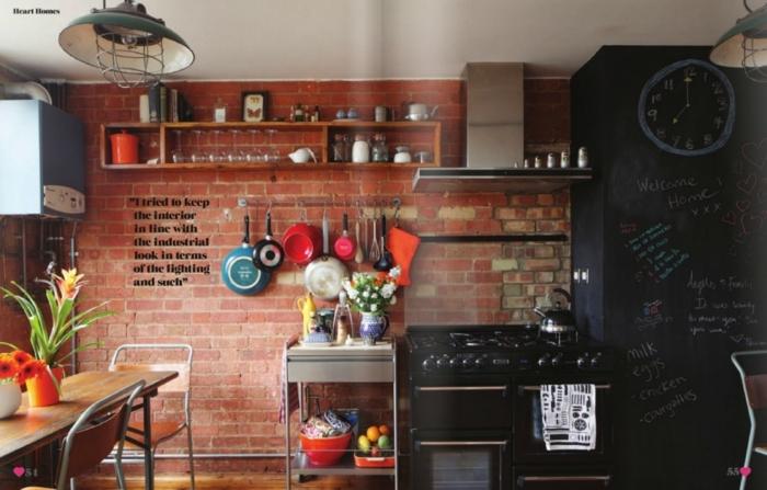 cocina moderna con elementos originales y muebles cocina en negro, pared de ladrillos y muchos objetos decorativos vintage