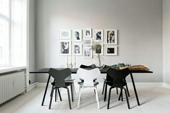 fotos originales, comedor moderno decorado en blanco y negro, grande mesa de madera en negro y pared decorada con fotos en blanco y negro en marcos blancos