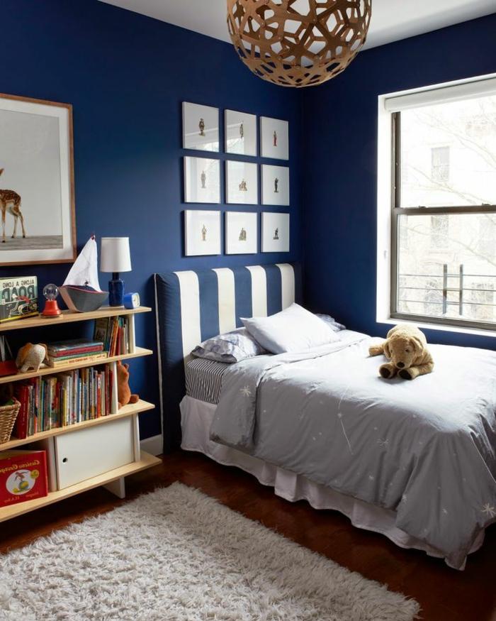 cuarto infantil decorado en blanco y azul navy, cama individual con cabecero en rayas, paredes en azul decoradas con cuadros modernos minimalistas