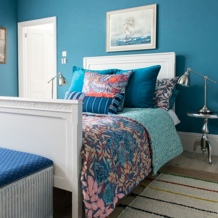 cama individual de madera pintada en blanco con cabecero, paredes pintadas en azul turquesa y decoradas con cuadros modernos