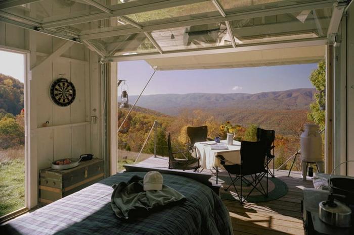 mini casas sobre ruedas, vivienda mínima de madera pintada en blanco con grande plataforma, terraza con mesa y sillas