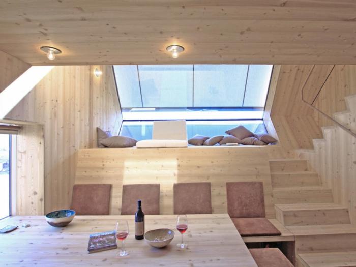 mini casa, interior de una vivienda mini, revestimiento de madera y lámparas empotradas, techo inclinado con grande ventanal
