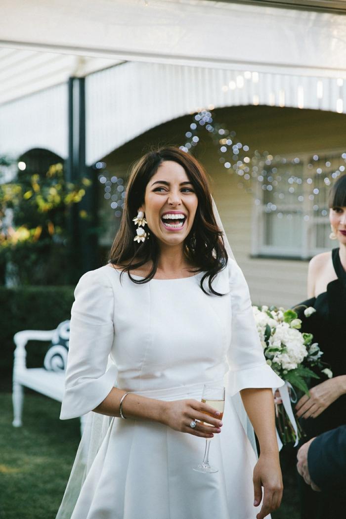 vestidos boda civil, vestido de novia blanco con largas mangas, tulo en el peinado y pendientes llamativos, pelo suelto ligeramente ondulado