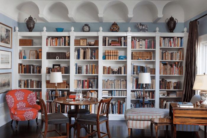 librería clásica de madera blanca, baldas de madera, salón con sillón rojo y mesa redonda, paredes en blanco y azul celeste, decoración con jarrones de barro