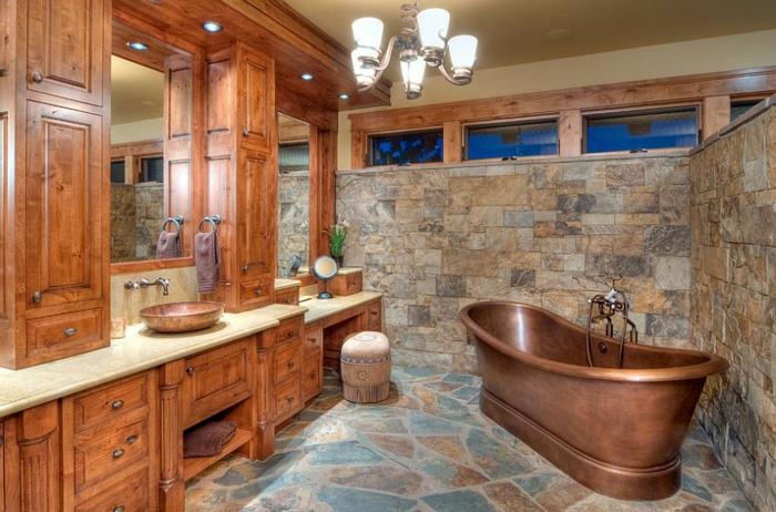 azulejos para baños que imitan piedra, baño en estilo rústico con bañera exenta vintage de cobre y muchos armarios de madera, candelabro vintage