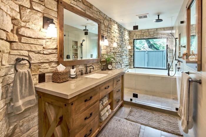 grande baño decorado en tonos beige con muebles y objetos decorativos de madera, paredes revestidas de piedra , azulejos para baños en beige