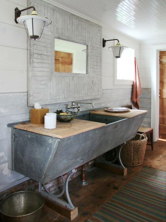 estilo rústico moderno, muebles auxiliares de baño, lavabo grande de obra con encimera de madera, espejo grande con marco de palets, suelo de tarima tapete