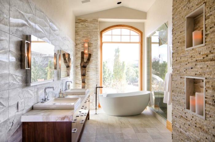 baño con luz natural, decoración moderna, muebles auxiliares, paredes de piedra, bañera ovalada, lavabo doble con espejos grandes