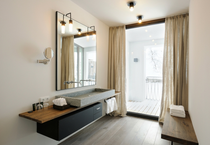 ba;o en beige, lavabo grande de granito, espejo cuadrado, mueble baño, color negro de madera, ventanal con cortinas, terraza