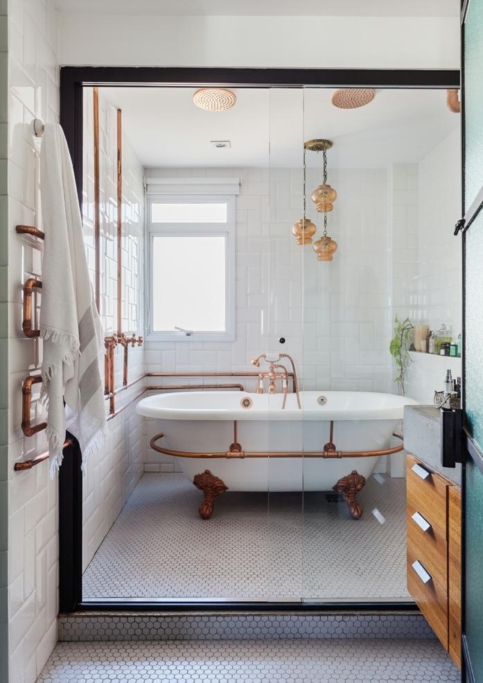 baño blanco, bañera con tubos en cobrizo, mámpara de vidrio, mueble baño, madera, lámpara colgante, ladrillo cisto esmaltado, luz natural